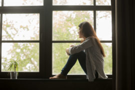 Thoughtful,Girl,Sitting,On,Sill,Embracing,Knees,Looking,At,Window,