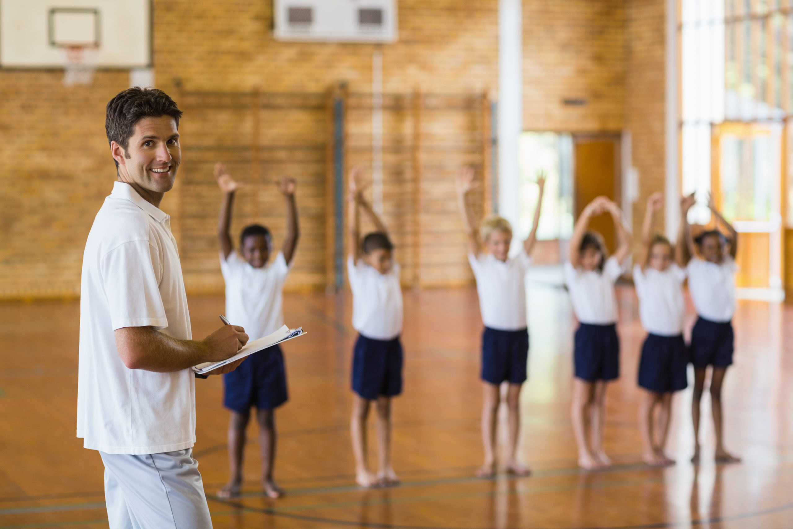 Sports,Teacher,Writing,Notes,On,Clipboard,While,Students,Exercising,In